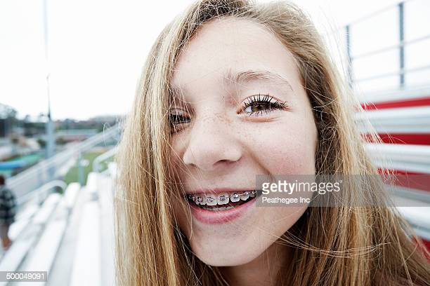 teenage girl smiling on bleachers - only teenage girls stock pictures, royalty-free photos & images