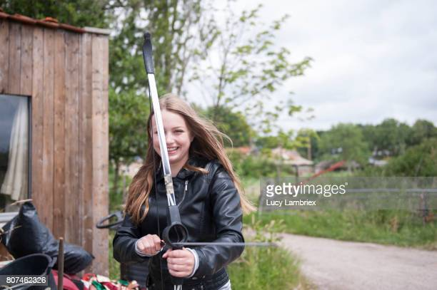 Teenage girl smiling with bow and arrow in her hands
