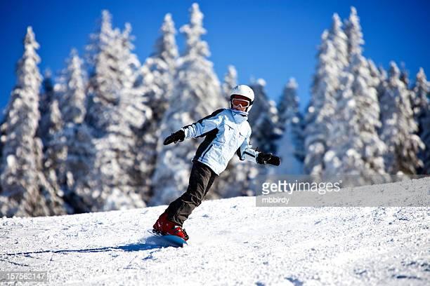 Teenage girl snowboarding on sunny winter day