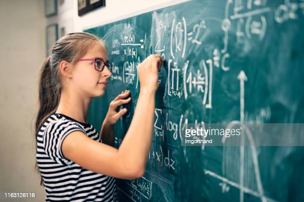 teenage girl solving advanced mathematical problems - mathematics stock pictures, royalty-free photos & images