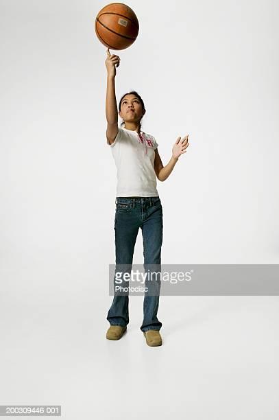 Teenage girl (13-14), spinning basketball on finger, posing in studio, portrait
