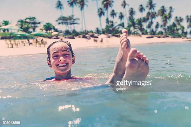teenage girl splashing in brazilian tropic sea