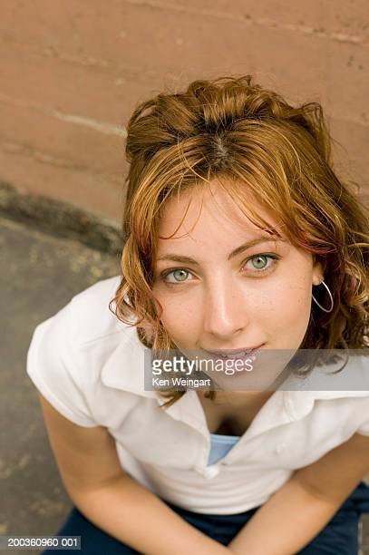 teenage girl (13-15) squatting, smiling, portrait, elevated view - green eyes stock pictures, royalty-free photos & images