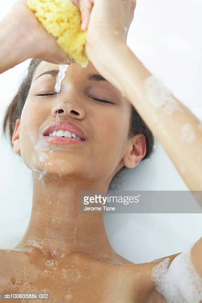 Teenage girl (16-17) squeezing water from sponge over face, eyes closed