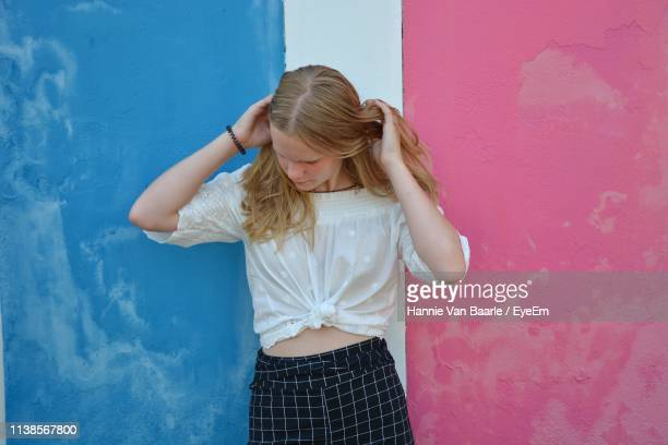 Teenage Girl Standing Against Colorful Wall