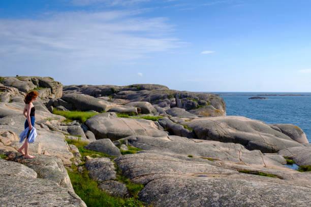 Teenage girl standing alone on rocky coast