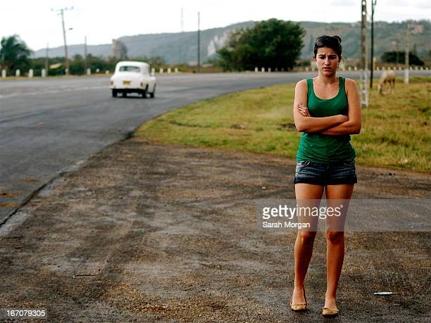 Teenage girl standing at the side of the road in a semi rural area on the outskirts of Havana, Cuba. There is no traffic apart from one vintage car...