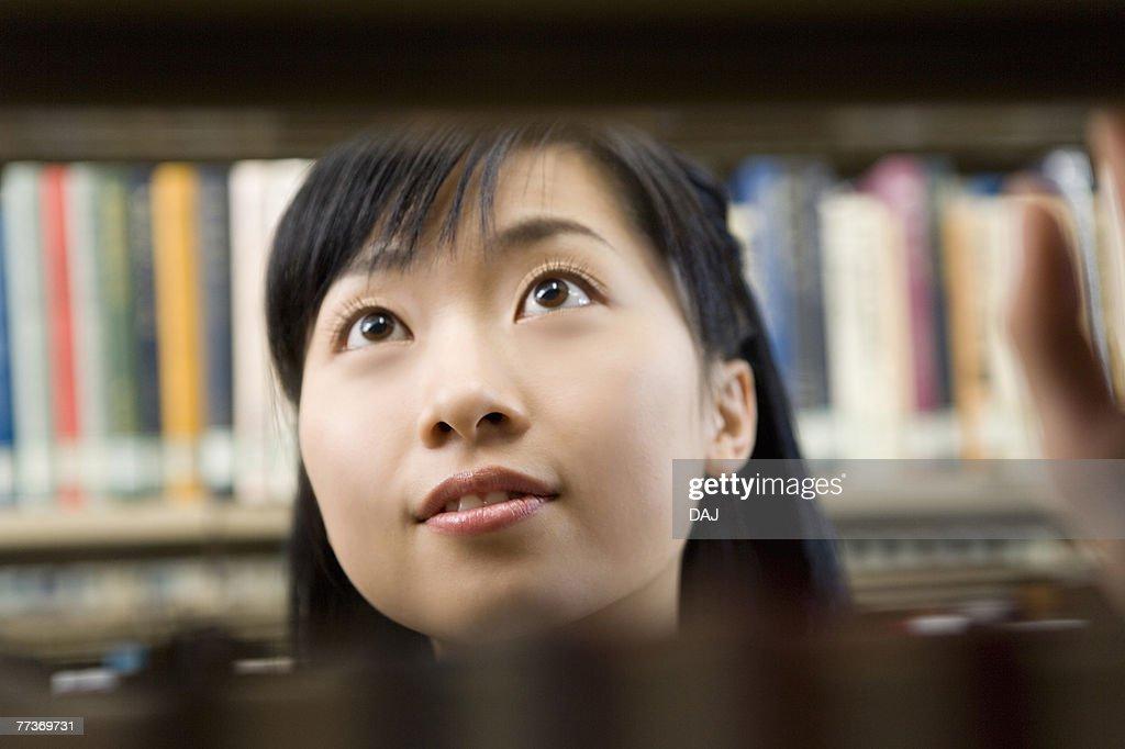 Teenage girl standing between bookcases : Photo