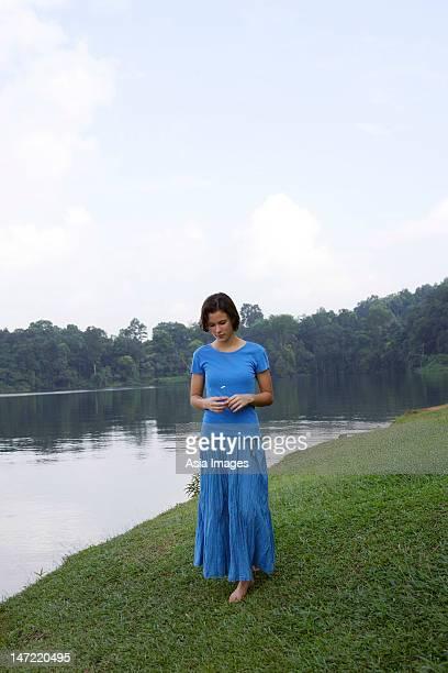 teenage girl standing by lake - alleen tienermeisjes stockfoto's en -beelden