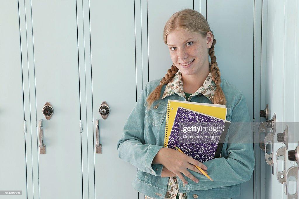 Teenage girl standing by lockers at school : Stockfoto