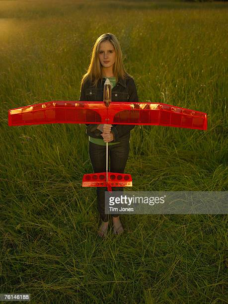 Teenage girl (16-17) standing holding model glider in field, elevated