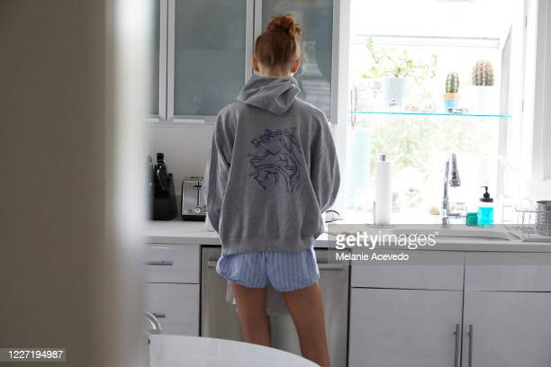 teenage girl standing in a kitchen with her back towards the camera. - 18 19 años fotografías e imágenes de stock