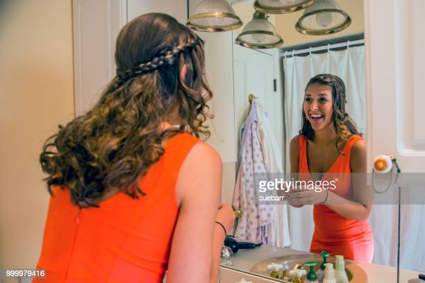 teenage girl standing in bathroom putting on jewelry - girl in mirror stock-fotos und bilder