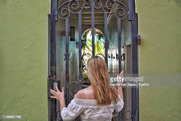 Teenage Girl Standing In Front Of Closed Gate