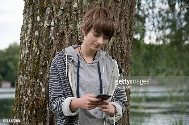 Teenage girl standing in front of tree trunk listening music with earphones