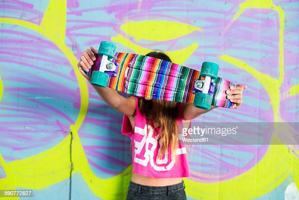 Teenage girl standing in front of wall with graffiti hiding behind colorful skateboard