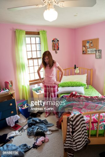 Teenage Girl Standing In Her Messy Room Stock Photo