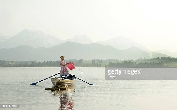 teenage girl standing in rowing boat with watering can on alpine lake