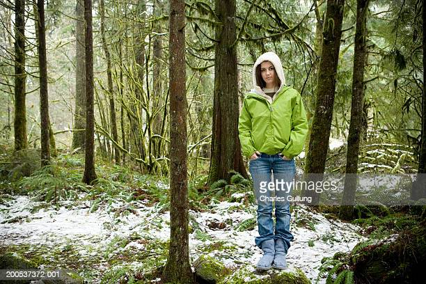 teenage girl (14-16) standing in snowy forest, hands in pockets - hands in pockets stock pictures, royalty-free photos & images