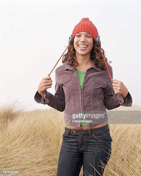 Teenage girl (16-18) standing in tall grass, smiling, portrait
