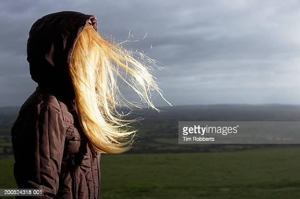 Teenage girl (16-18) standing in wind in farm field, side view