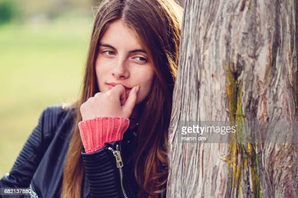 Teenage girl standing near a tree