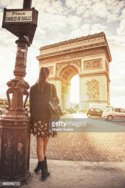 a teenage girl standing near the arc de triomphe in paris, france - champs elysees quarter stock pictures, royalty-free photos & images