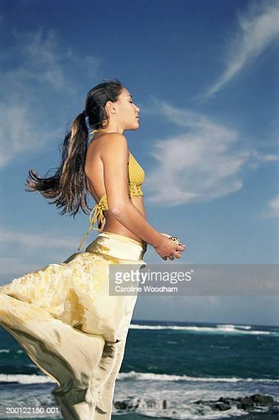Teenage girl (16-18) standing on beach, holding seashell, side view