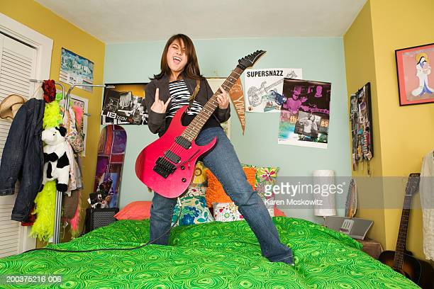 Teenage girl (14-16) standing on bed, holding electric guitar, yelling