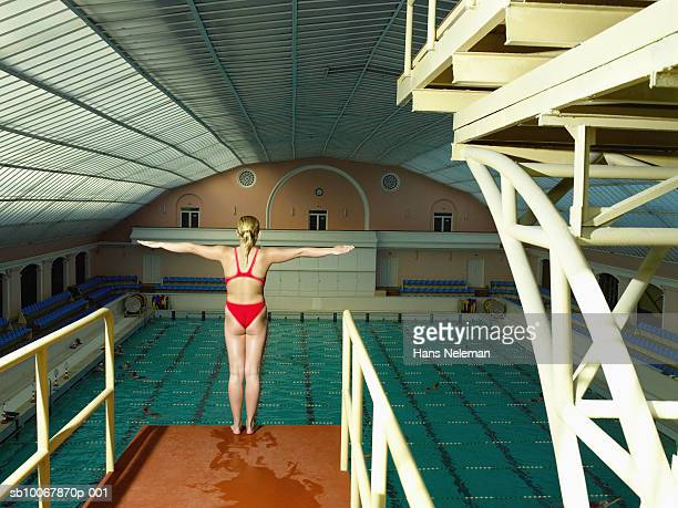 Teenage girl (14-15) standing on dive platform, rear view