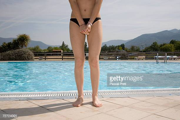 Teenage girl (13-15) standing on edge of pool, low section