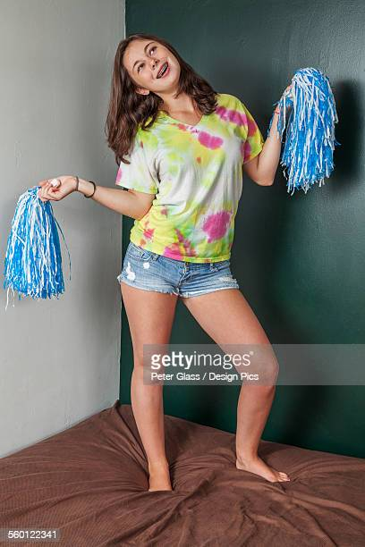 teenage girl standing on her bed holding pom-poms - barefoot photos stock photos and pictures