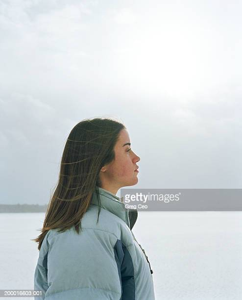Teenage girl (15-17) standing outdoors, profile, winter