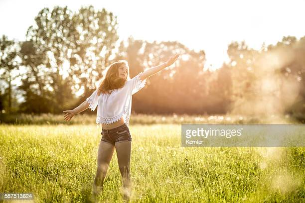teenage girl standing with arms outstretched in meadow - hot pants stock-fotos und bilder