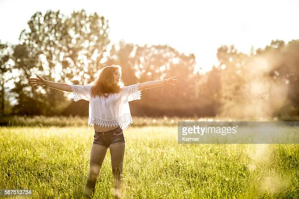 teenage girl standing with arms outstretched in meadow - hot pants stock pictures, royalty-free photos & images