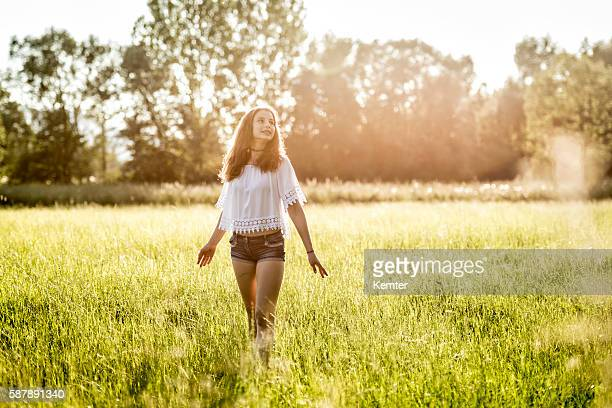 teenage girl standing with arms outstretched in meadow - hot pants stock photos and pictures