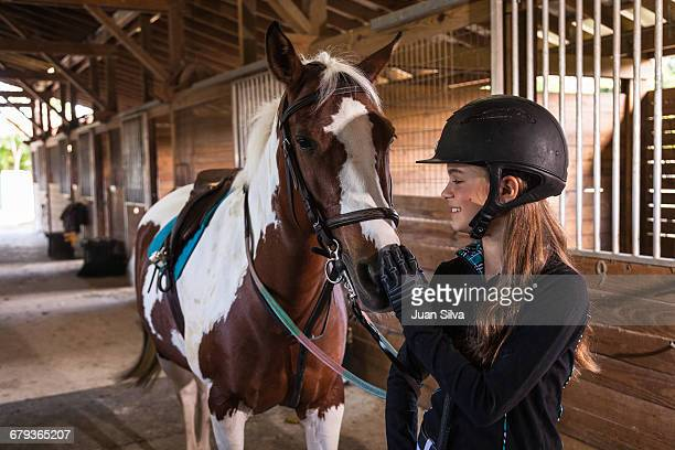 teenage girl standing with horse in a stable - riding hat stock pictures, royalty-free photos & images