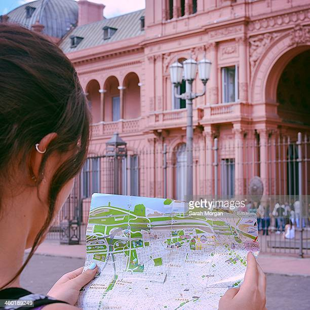 Teenage girl stands in front of the Casa Rosada in Buenos Aires, Argentina. She is looking at a map of the city which she is holding in her hands....