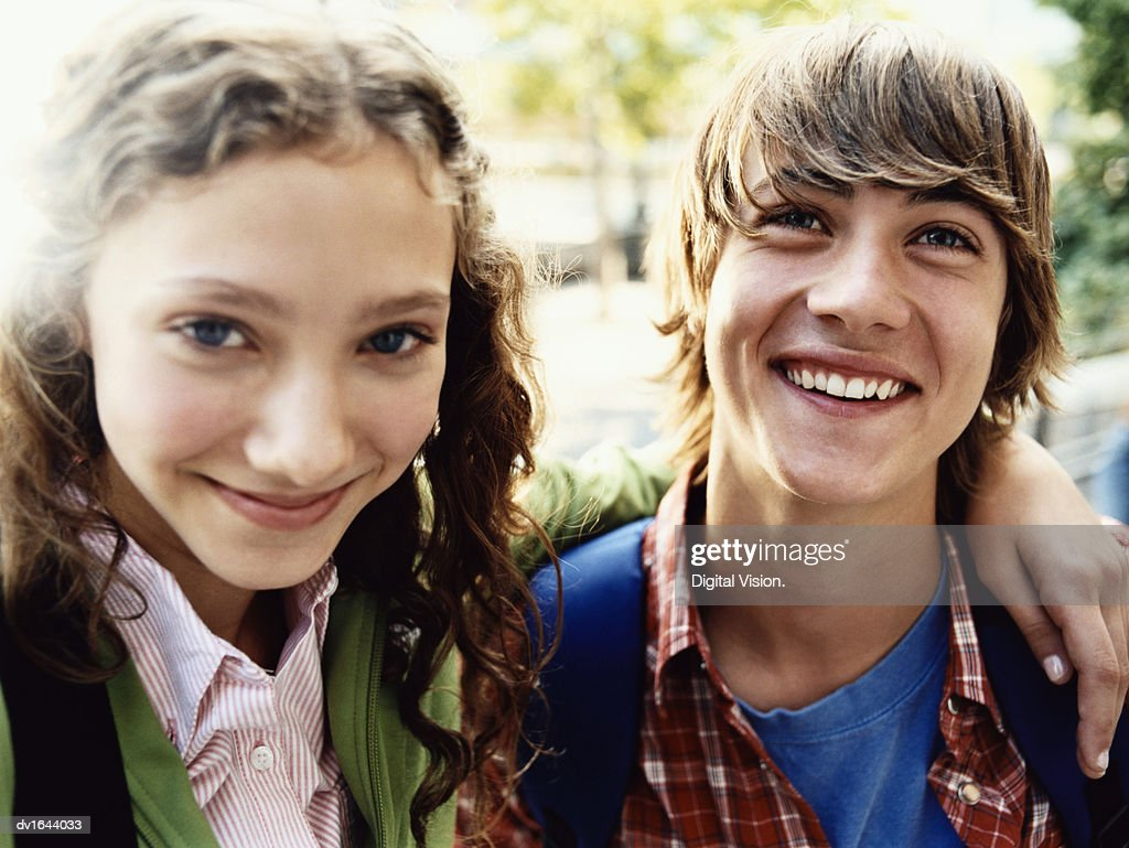 Teenage Girl Stands Smiling With Her Arm Around Her Friend : Stock Photo