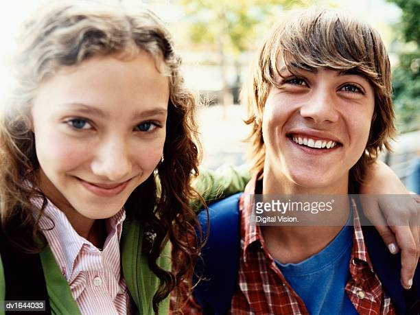 teenage girl stands smiling with her arm around her friend - schulkind stock-fotos und bilder
