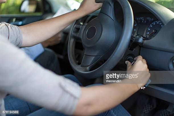 Teenage girl starting a car