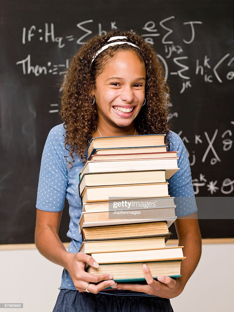 Teenage girl student posing in classroom with stack of books : Stock Photo