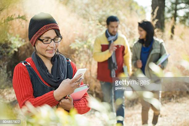 teenage girl student reading sms on smart phone in outdoor. - nepalese ethnicity stock pictures, royalty-free photos & images
