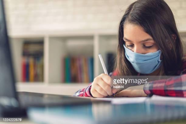teenager-mädchen studieren zu hause während covid-19 pandemie - schulische prüfung stock-fotos und bilder