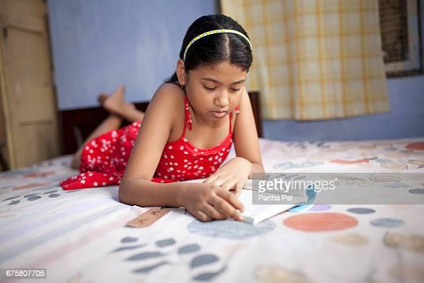 Teenage girl studying inside home