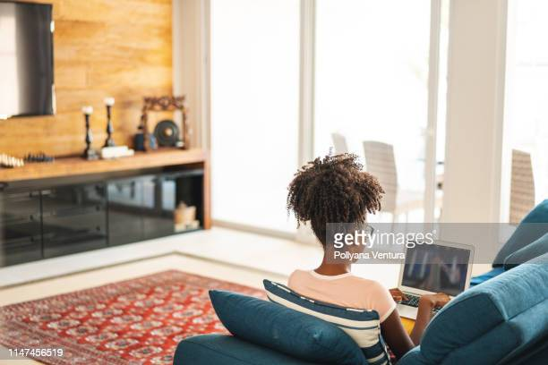 teenage girl studying on laptop in living room - looking at camera stock pictures, royalty-free photos & images