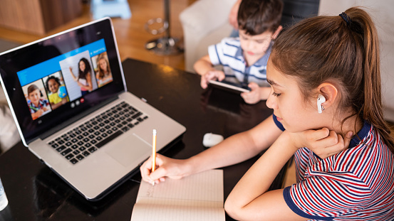 Teenage girl studying with video online lesson at home   family in isolation Homeschooling and distance learning 1216391310
