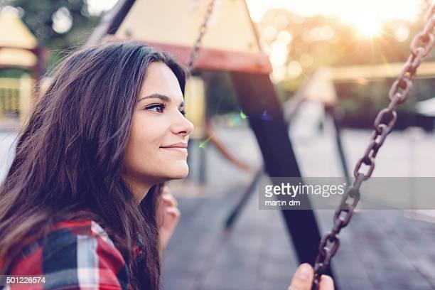 Teenage girl swinging outside