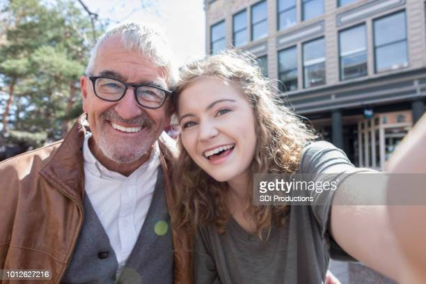 teenage girl takes selfie with grandfather - grandparent stock pictures, royalty-free photos & images
