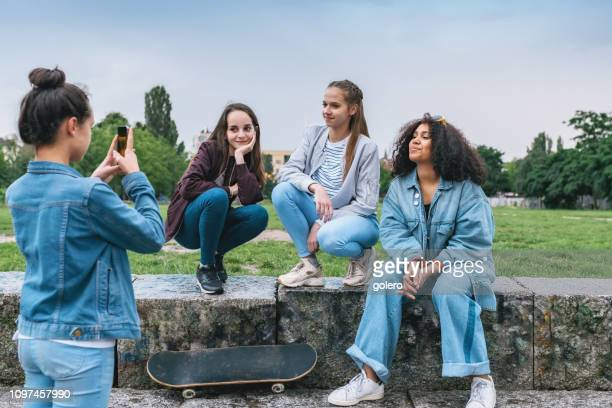 teenage girl taking photo of girlfriends with mobile - bomber jacket stock pictures, royalty-free photos & images